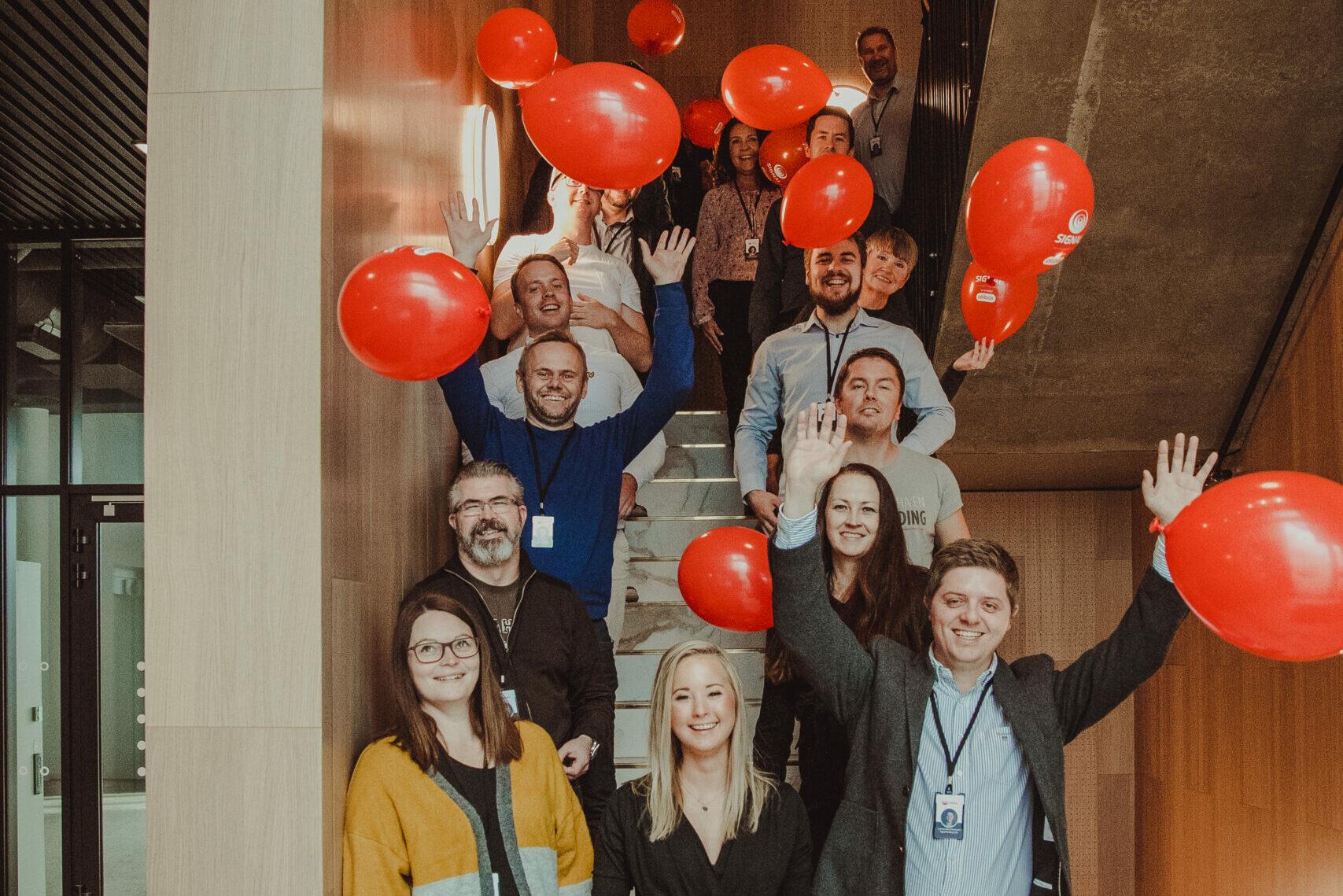 En gjeng fra Signal står oppstilt i en trapp og feirer med røde ballonger