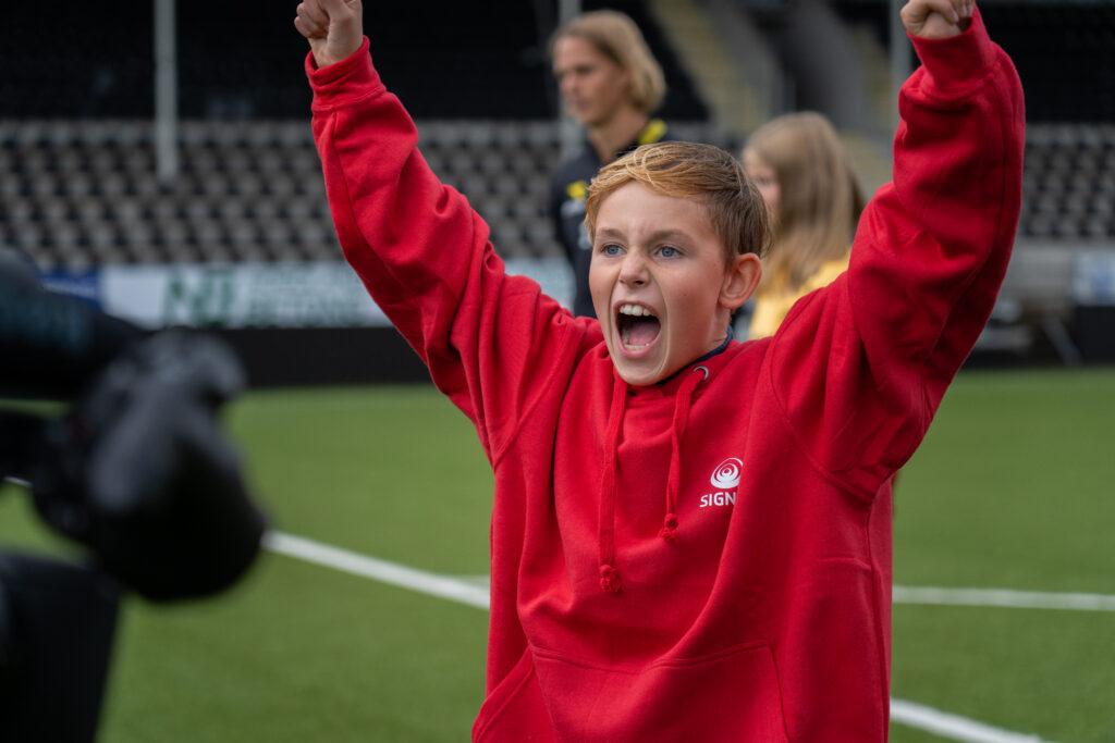 Bodøgutt ikledd rød Signal-genser jubler over mål på fotballbanen under Drømmetreffet 2020