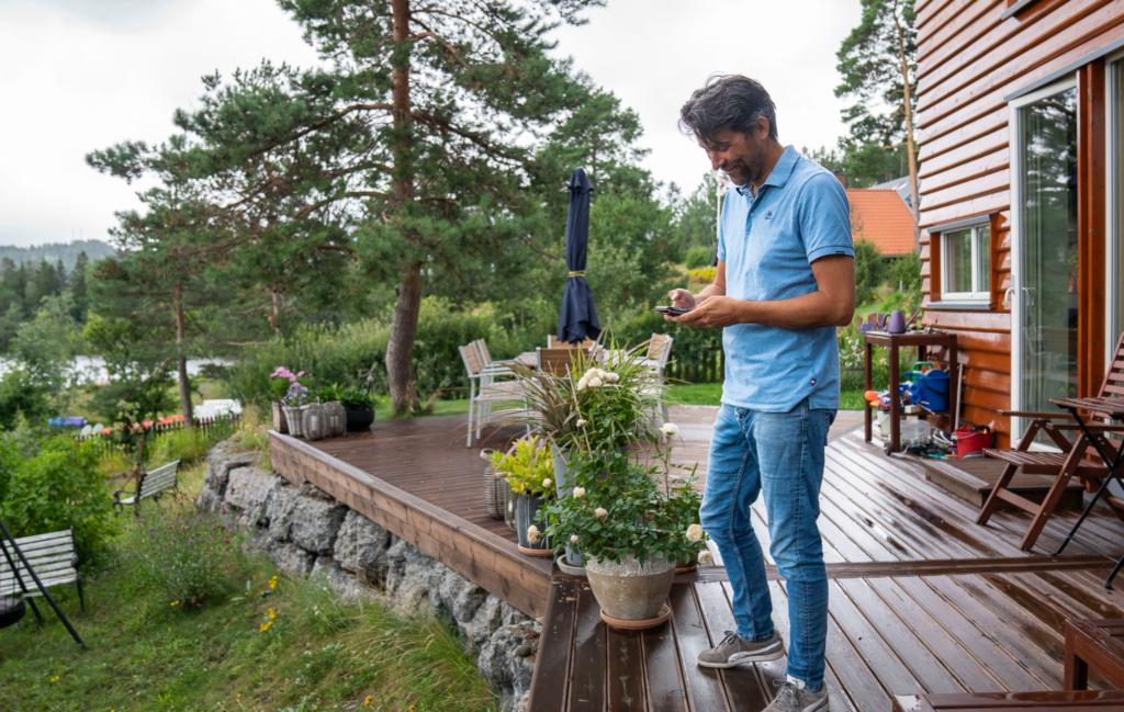 Mann står på terrassen i hagen og kikker ned på telefonen sin