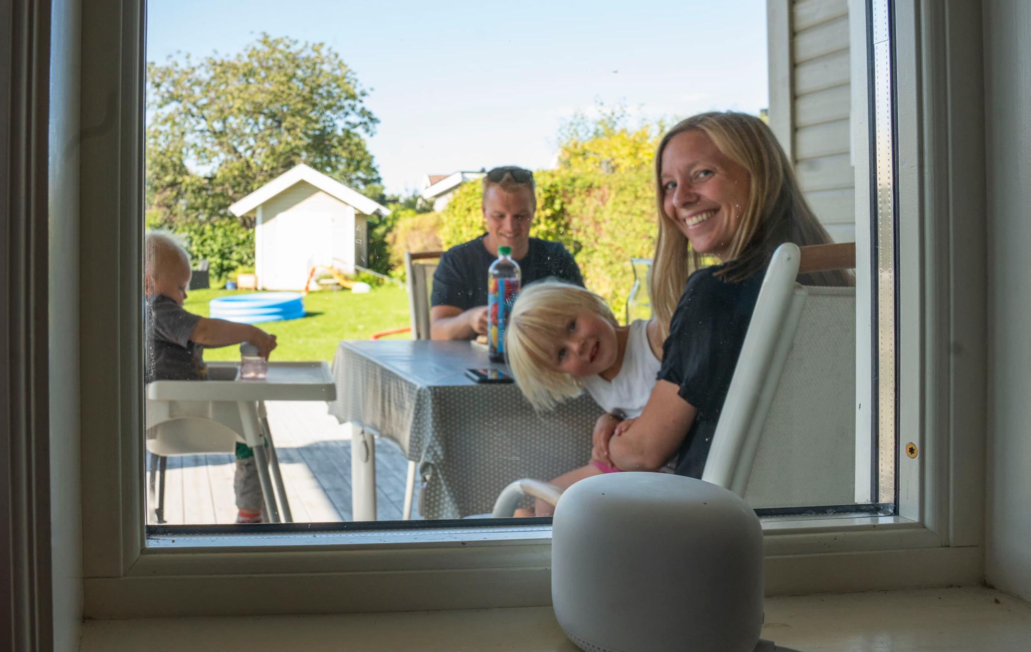 Google Nest Wifi i vinduskarmen. Gjennom vinduet sees en småbarnsfamilie sittende på terrassen.