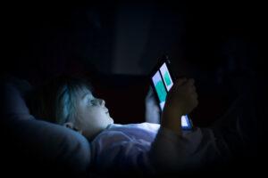 Liten jente ligger i mørket og ser på nettbrettet sitt