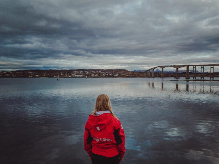 Jente i rød Signal-jakke ser ut over havet og brua mellom Finnsnes og Silsand