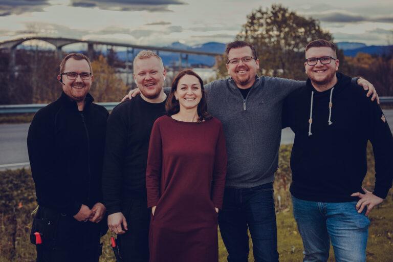 Senjanett AS sine ansatte står sammen og smiler med Finnsnesbrua i bakgrunnen