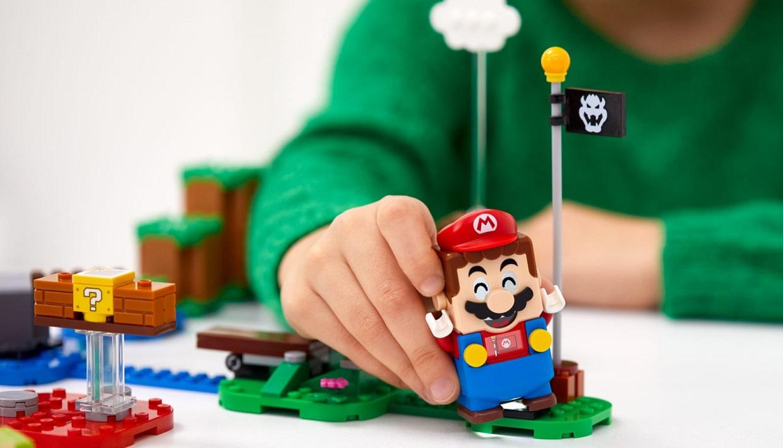 Et barn i grønn genser leker med Super Mario figurer