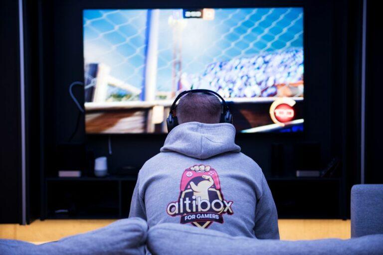 Gutt sitter foran tv-skjermen og gamer, med grå altibox-genser på