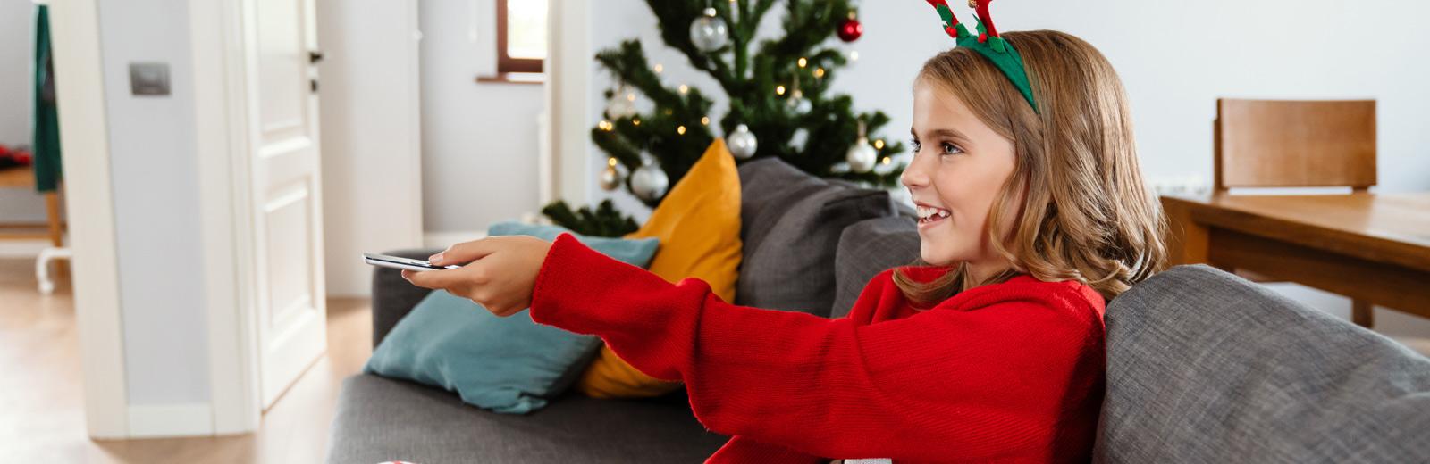 Julepyntet jente retter fjenkontrollen mot tv i spenning når hun slår på julefilm
