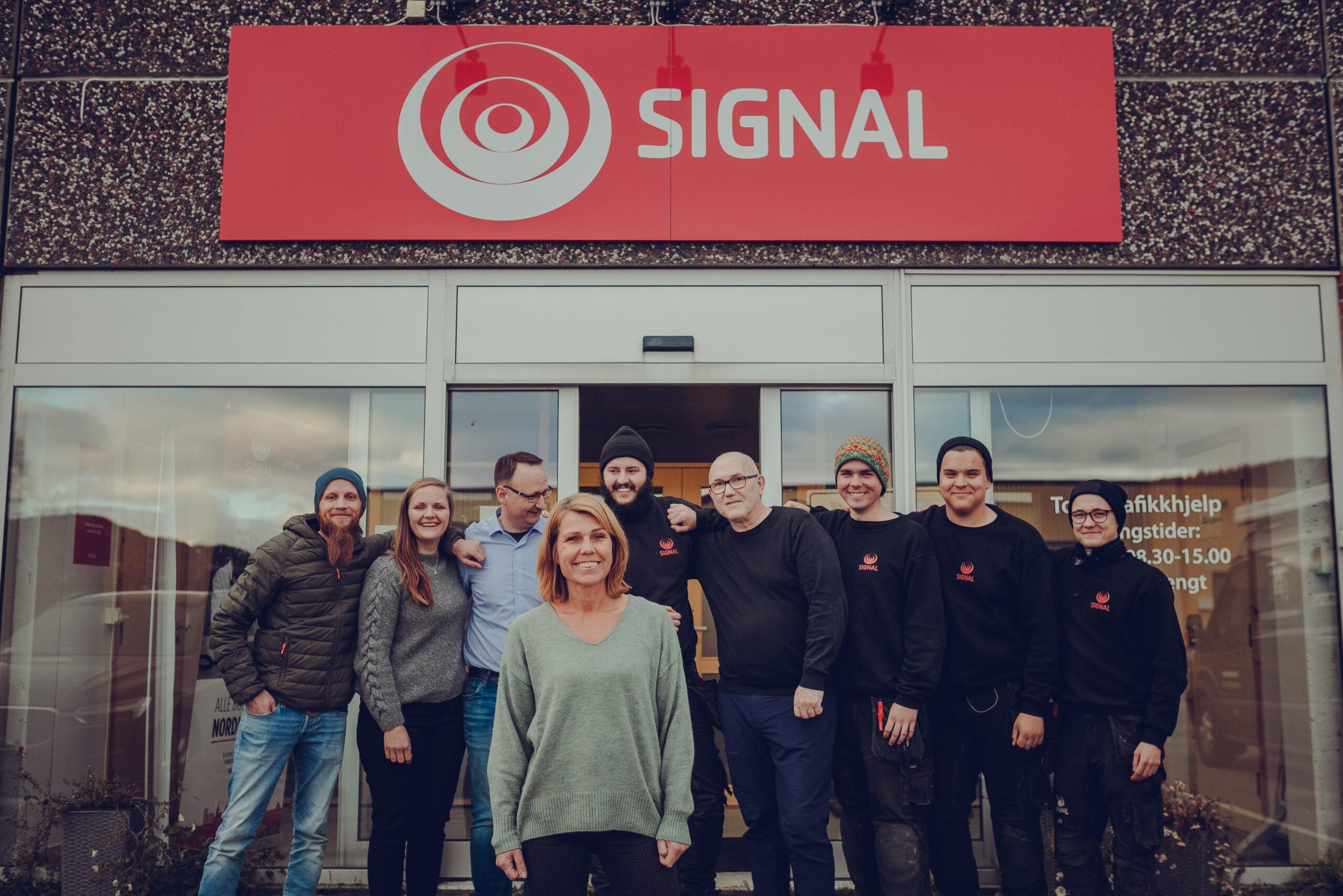 De ansatte i Signal Bredbånd avdeling Mosjøen står ved inngangspartiet under det røde Signal-skiltet.