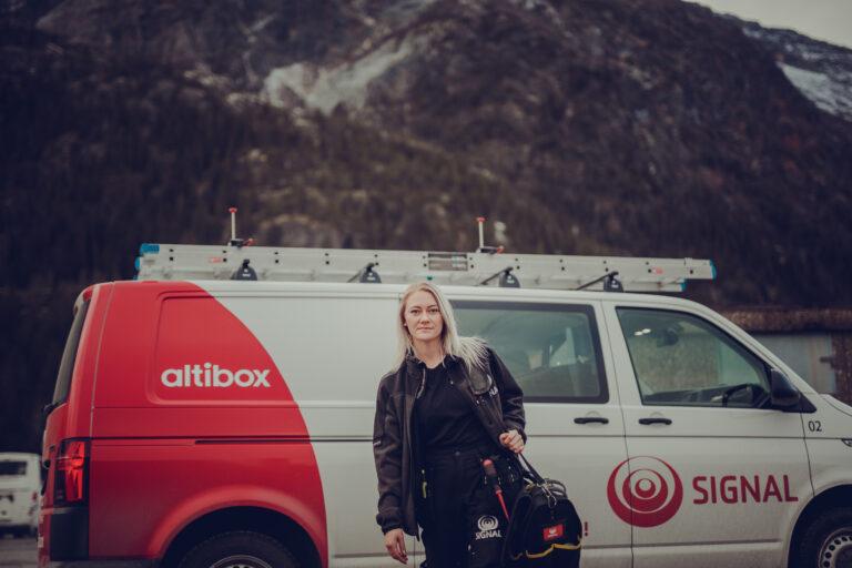Lærlingen Betty fra Signal Bredbånd er på oppdrag med Signals bil i bakgrunnen
