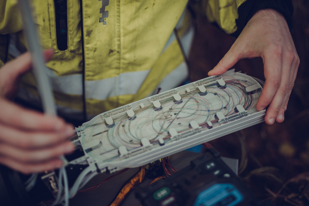 Telemontør åpner fiberboks ute i felten for å sjekke om alt er i orden