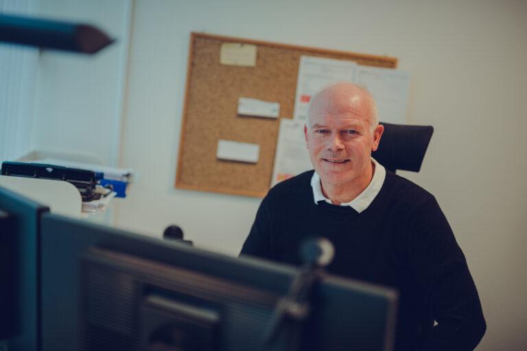Prosjektleder Kåre Berglund sitter bak dataskjermen på kontoret i Signal Bredbånd, Narvik