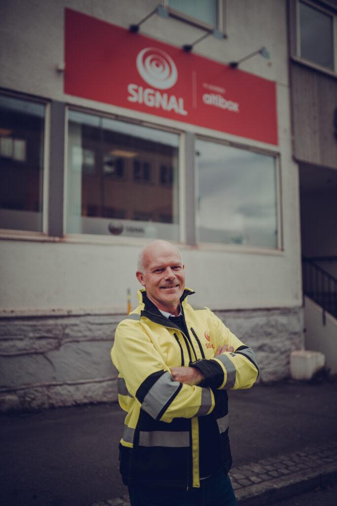 Kåre Berglund står i arbeidsjakka foran Signal-kontoret i Narvik