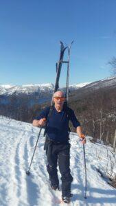 Kåre Berglund går med randonee-skiene på ryggen på snødekt landskap på vei opp et fjell