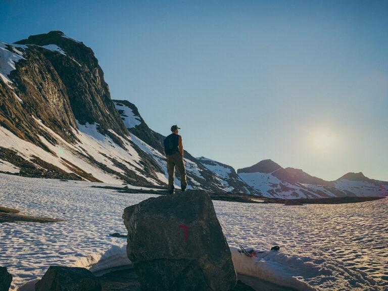 Mann står på en turistforening-sten med fjell i bakgrunn og soler seg