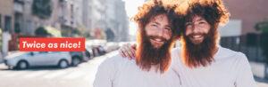 To skjeggete tvillinger holder rundt hverandre i en solfylt gate